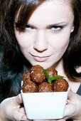 Young woman with bowl of chocolates