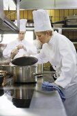 Female chef checking the contents of a pan