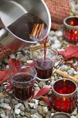 Pouring mulled wine into glasses