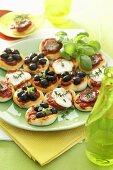 Mini-pizzas with olives, mozzarella and ham