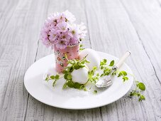 Boiled eggs, salt and posy of blossom on plate