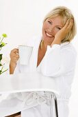 Blond woman sitting at table with a cup of cappuccino