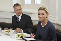 Businessman with secretary eating in a restaurant