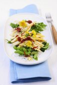 Roasted white asparagus with dried tomatoes on a rocket salad