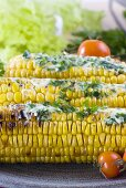 Three grilled corn cobs with herb butter