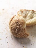 A sesame seed roll, broken