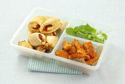 Tomato pastries, chicken fingers and watercress in a plastic box