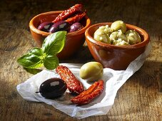 Dried tomatoes, olives and basil on a wooden surface