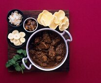 Beef curry in pot with mini-poppadoms and accompaniments