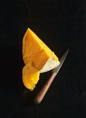 A piece of Mimolette with knife (French hard cheese)