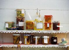 Jars of jam, jelly and relishes, bottles of liqueur on shelves