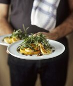 Man holding plates of pumpkin with melted cheese and rocket