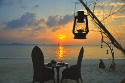 A romantic candlelight dinner on the beach at sunset