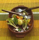 Half-eaten root vegetable salad in wooden bowl