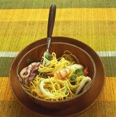 Seafood salad with spaghetti in wooden bowl