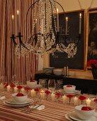 Festively set table below chandelier