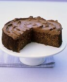 Chocolate cake with pieces removed on cake stand