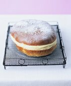 Yeast cake filled with vanilla cream on a cake rack