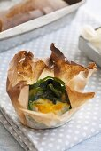 Baked egg with spinach in papillotes