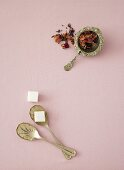 Dried flowers in a tea strainer and a sugar cube on a spoon