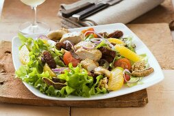 A winter salad with chicken, dried fruits and oranges