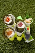 Temaki sushi with salmon, tuna and carrot sticks