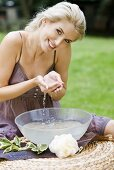 A blonde woman scooping water out of a bowl