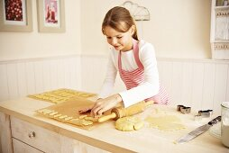 Girl placing cut-out biscuits on baking parchment