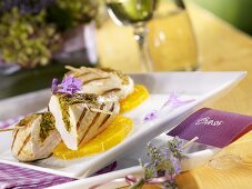 Grilled chicken breast filled with herbs on orange slices