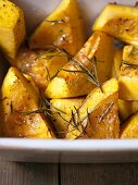 Oven-baked pumpkin pieces with rosemary