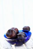Plums in glass bowl on wooden chair