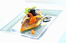 Fried sea bass with squid ink pasta