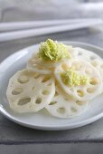 Slices of pickled lotus root with fresh wasabi