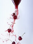 Cherry juice and cherries pouring out of a bottle
