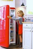 Little girl opening refrigerator
