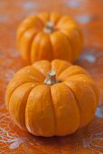 Two pumpkins on cobweb-patterned tablecloth
