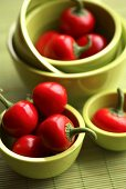 Several cherry peppers in green bowls