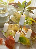 Decoration for autumn buffet: pumpkins & candles on tiered stand