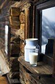 Milk can & glass of milk on window sill of Alpine chalet