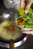 Seasoning food in wok with Thai basil and chillies (Thailand)