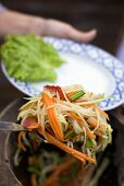 Putting vegetable salad on plate (Thailand)