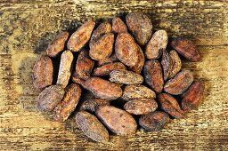 Cocoa beans on wooden background (overhead view)