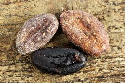 Three cocoa beans on wooden background