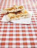 Pieces of focaccia on napkin on checked tablecloth