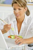 Woman eating vegetable salad with chopsticks at laptop