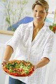 Woman holding platter of tomato salad