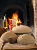 Pizza dough and ingredients in front of pizza oven