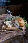 Partly sliced bread and nuts on rustic table