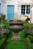Flowers in stone vase in country garden (house in background)