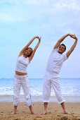 Man and woman doing exercises on beach